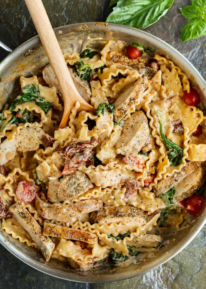 Silver skillet filled with creamy Tuscan Chicken Pasta with a wooden spoon in it.