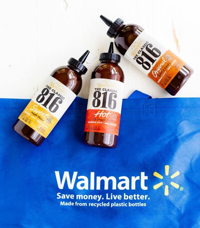Three bottles of 816 BBQ Sauce next to a reusable Walmart bag.