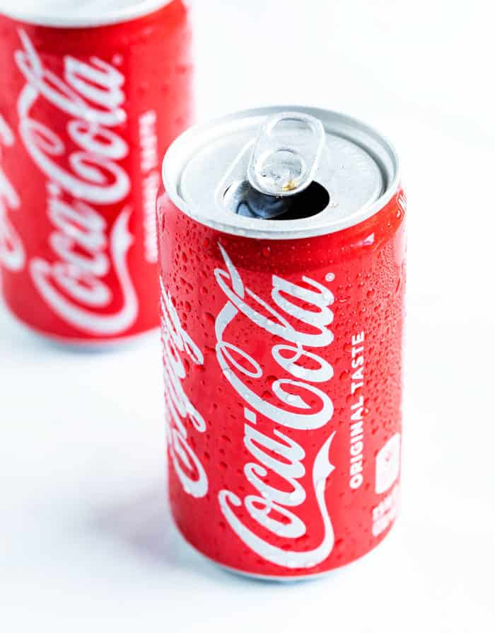 A cold can of cola cola popped open with a red can of coke behind it.