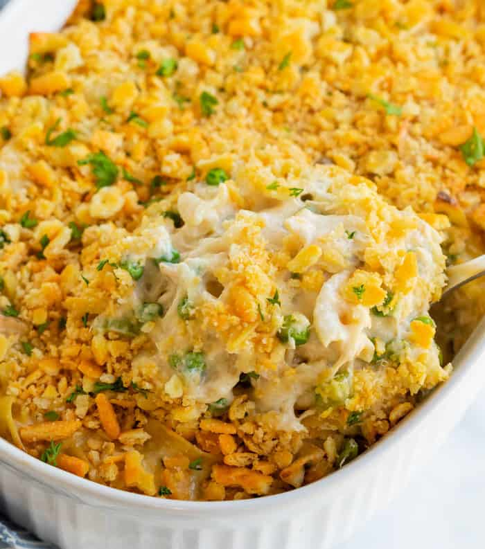 A spoon lifting up a big scoop of tuna noodle casserole from a casserole dish.