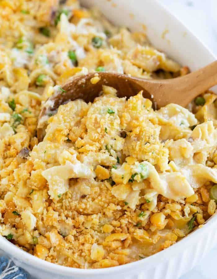 A wooden spoon in a casserole dish filled with tuna noodle casserole with egg noodles.