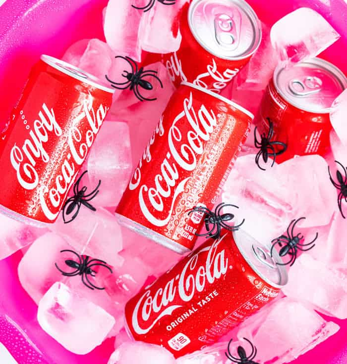 A pink ice bucket filled with mini cans of Coca Cola
