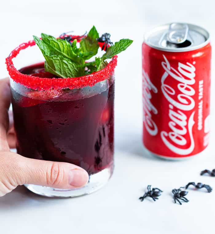A hand holding a glass of red sangria with a sugared rim and mint leaf next to a can of coke.