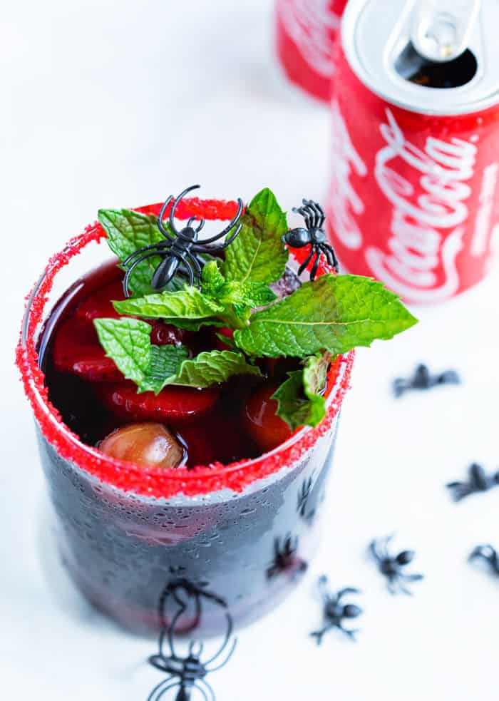 A glass with a sugared rim filled with red sangria topped with a mint leaf with a can of coke behind it.