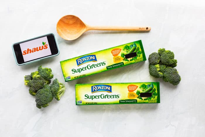 Two boxes of Ronzoni pasta with broccoli on a white surface next to a wooden spoon and a cell phone with the shaws logo.