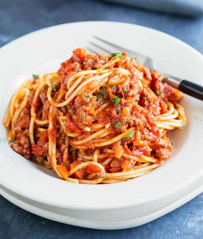 A white bowl filled with spaghetti Bolognese with a fork in the background.