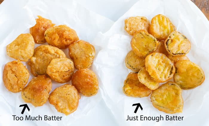 Two types of battered and fried pickles on white wax paper.