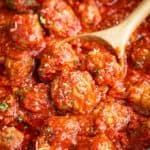 Italian meatballs sprinkled with Parmesan cheese being scooped by a wooden spoon.