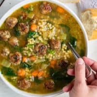 A white bowl full of Italian Wedding Soup with a hand holding a spoon.