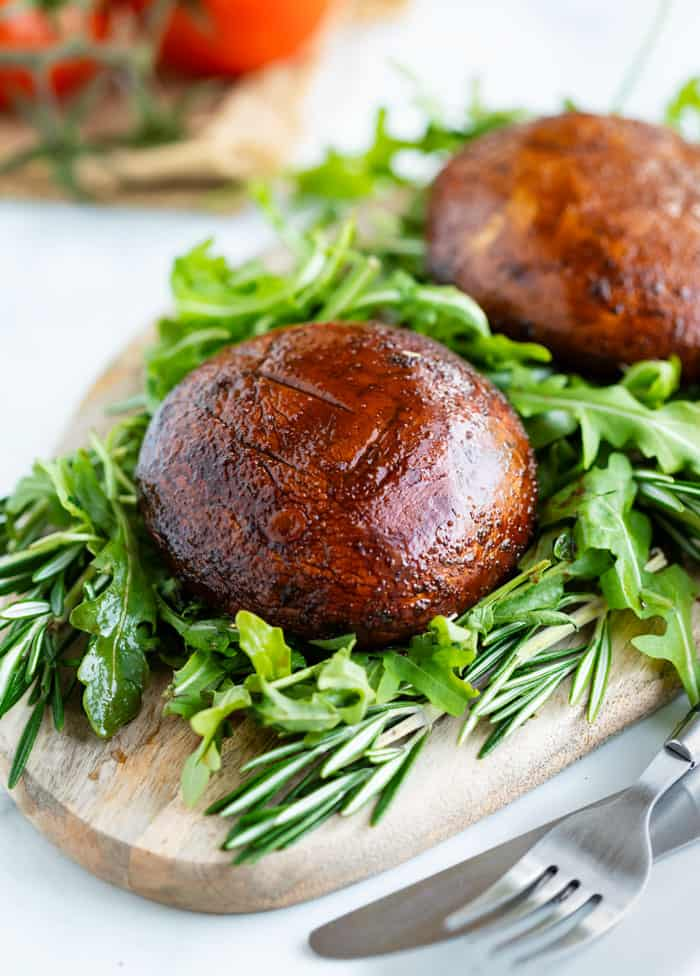 A grilled portobello mushroom on top of fresh greens next to rosemary on a cutting board.