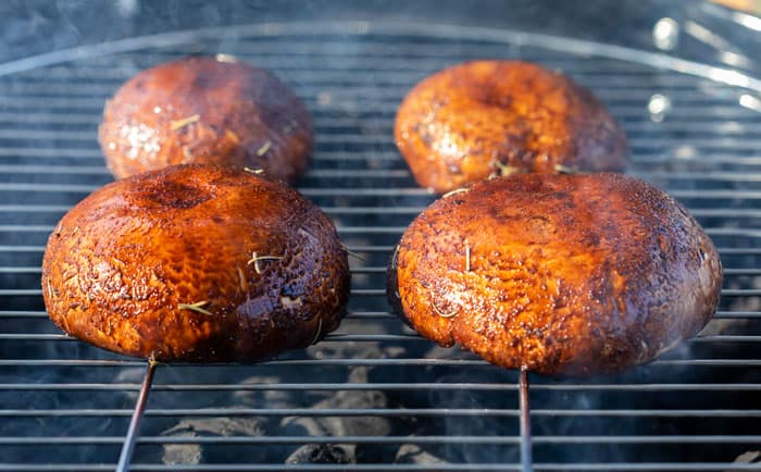 Four portobello mushrooms being cooked on a charcoal grill.