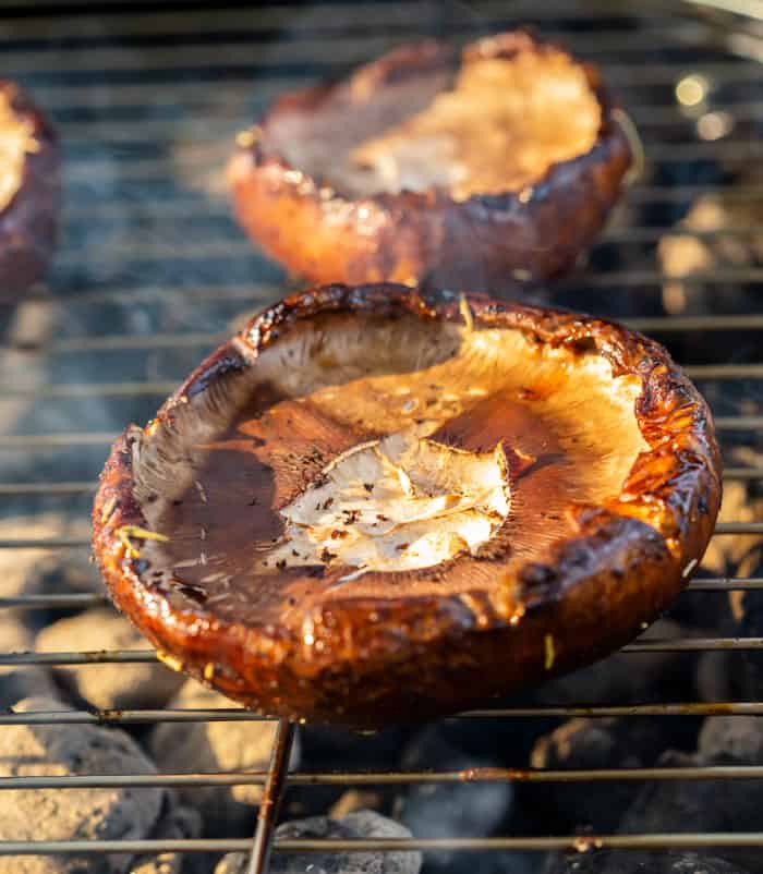 A portobello mushroom being cooked on a charcoal grill.