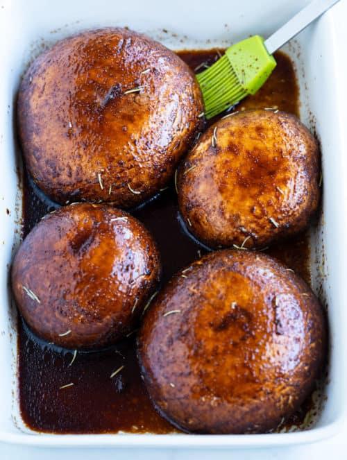 Portobello mushrooms marinating in a casserole dish.