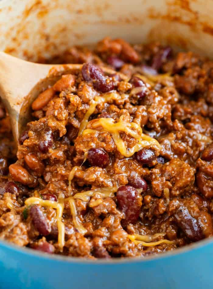 Close up view of a wooden spoon scooping chili out of a pot with melted cheese on top.