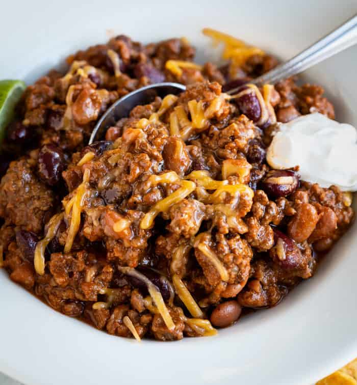 Chili in a white bowl with a spoon and melted cheese on top with sour cream.