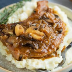 French Onion Smothered Pork Chops on a pile of mashed potatoes.