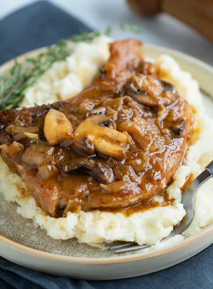 White potatoes on a plate topped with a pork chop smothered in a french onion sauce with mushrooms.