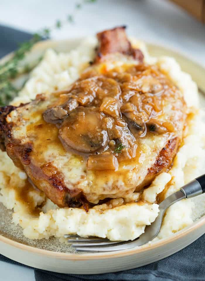 A Pork Chop on top of mashed potatoes topped with melted cheese and a french onion mushroom sauce.