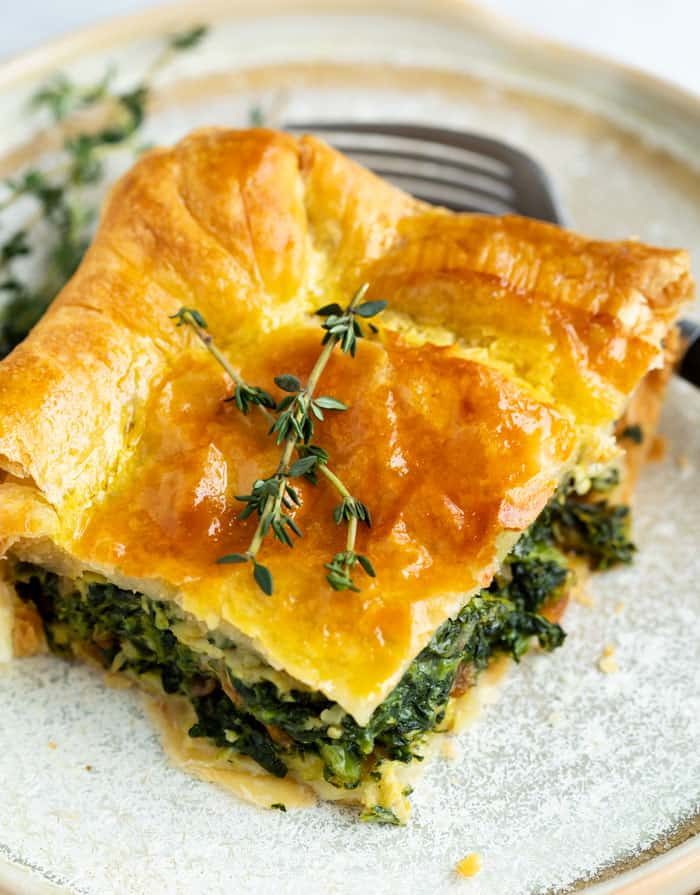 A slice of spinach pie with a golden brown puff pastry topping garnished with fresh thyme on a plate.