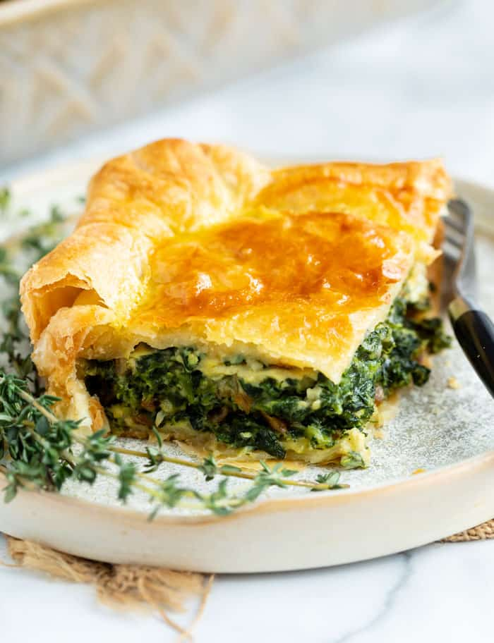 A slice of spinach pie on a plate with fresh thyme next to it and a fork on the side.