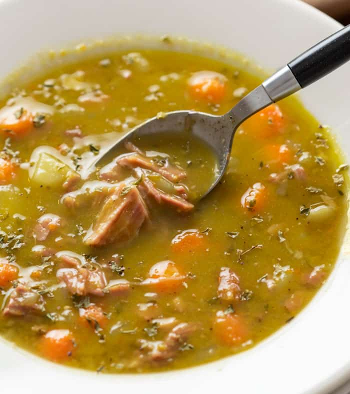 A white bowl of split pea soup with a spoon scooping some out.