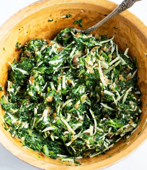 A mixing bowl of spinach pie filling ingredients mixed together.