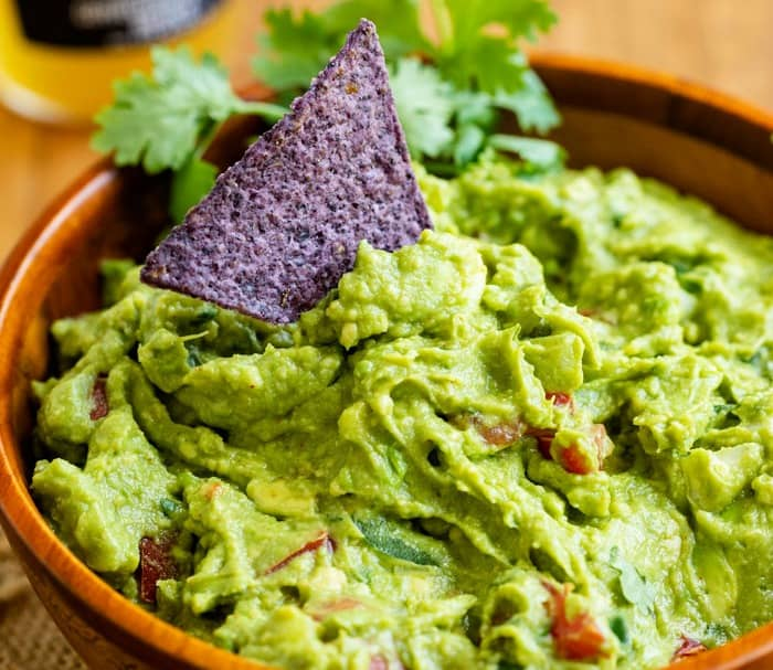 A tortilla chip dipping into a wooden bowl of guacamole with cilantro in the background.