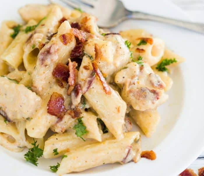 A white plate topped with penne in a creamy ranch sauce with chicken and bacon.