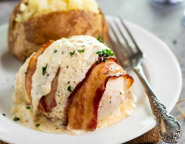 A white plate with a chicken breast with bacon wrapped around it and white sauce on top with a baked potato in the background.