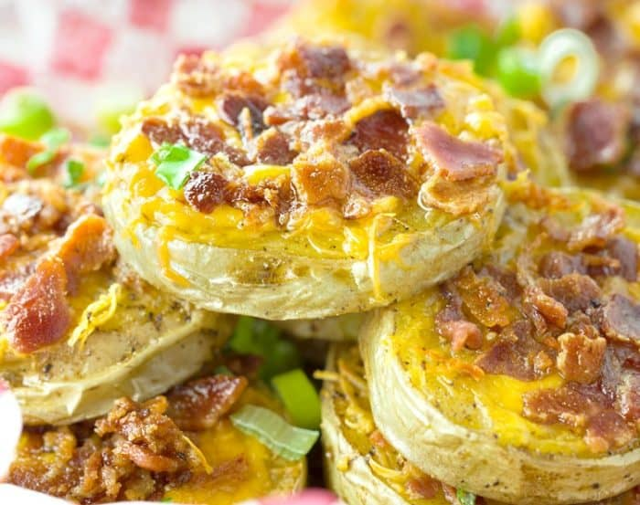 A pile of baked potato slices topped with melted cheese and crispy bacon.