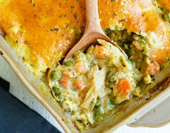 A casserole dish with a wooden spoon scooping out bisquick chicken pot pie.
