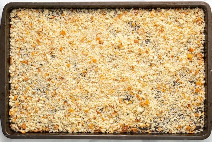 Homemade breadcrumbs on a baking sheet.