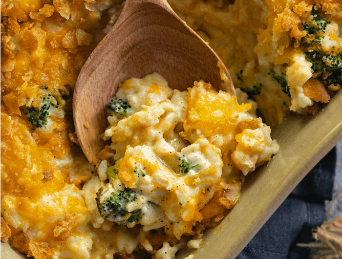 A wooden spoon scooping out broccoli cheddar chicken and rice casserole from a casserole dish.