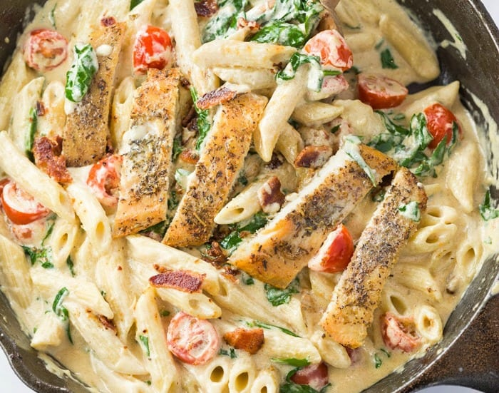 A cast iron skillet filled with creamy pasta topped with cherry tomatoes, spinach, and slices of seared chicken.