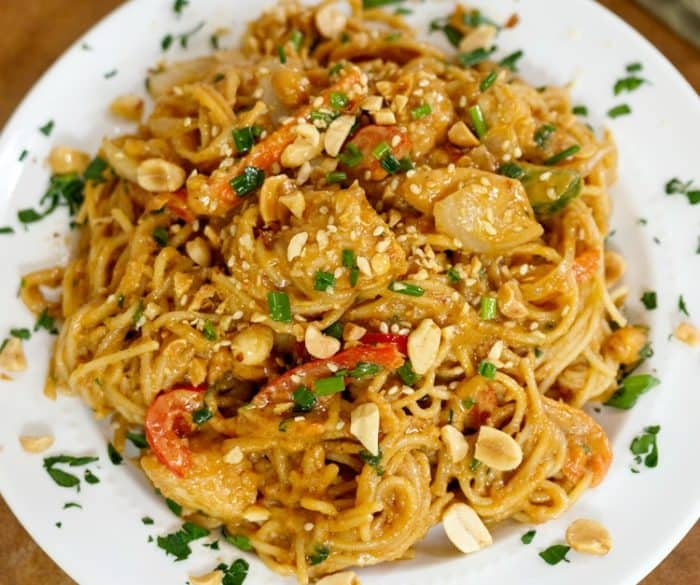 Spaghetti noodles, vegetables, and chicken in a peanut sauce on a white plate garnished with peanuts and parsley.