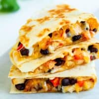 A stack of chicken quesadillas filled with melted cheese, black beans, and peppers.