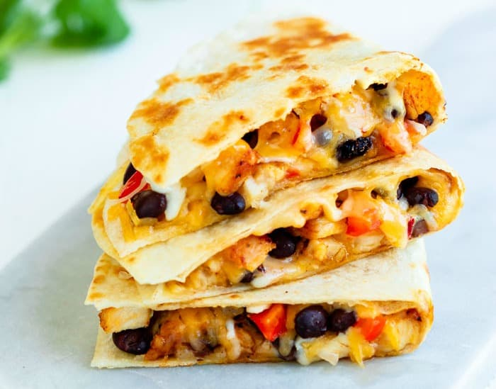 3 quesadillas stacked on top of each other on a white surface. Filled with black beans, chicken, and cheese.