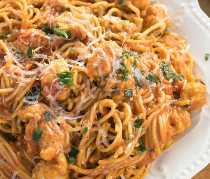 A white plate filled with spaghetti in a thick tomato gravy sauce with diced chicken and parsley.