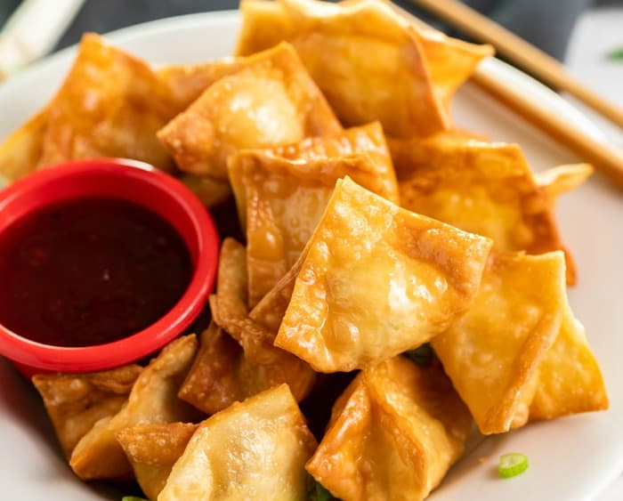 A white plate with a pile of crispy crab rangoon on top with a ramekin of sweet and sour sauce.