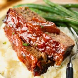 Cracker Barrel Meatloaf with glaze topped with ketchup sauce on top of mashed potatoes.