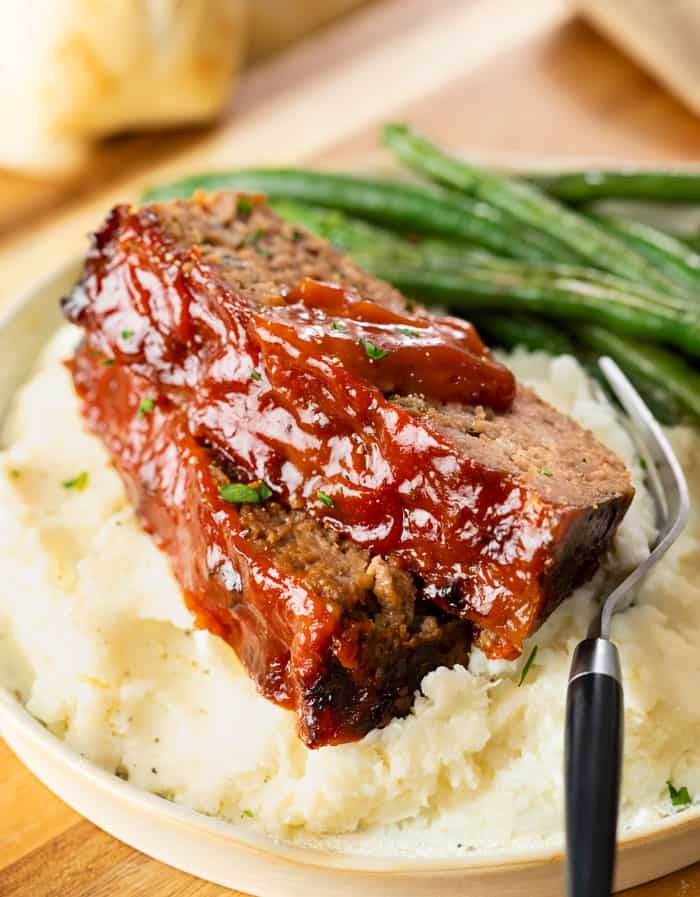 Cracker Barrel Meatloaf on a pile of mashed potatoes with green beans in the background.