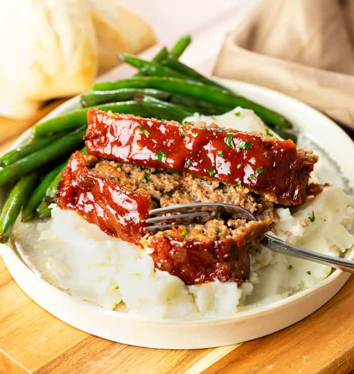 Two slices of Cracker Barrel meatloaf over mashed potatoes with green beans in the background.