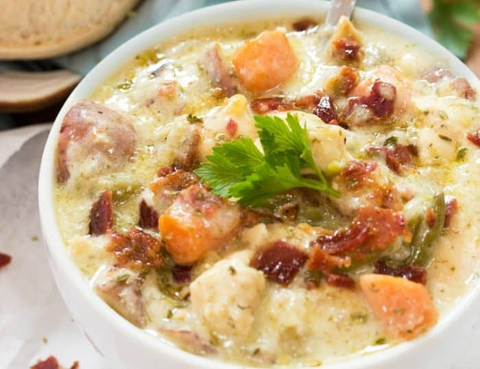 A white bowl filled with crock pot creamy chicken stew topped with bacon and parsley.