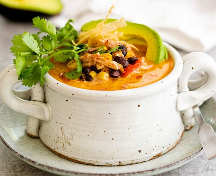 A white soup crock filled with creamy tortilla soup garnished with cilantro, tortilla strips, and an avocado slice.