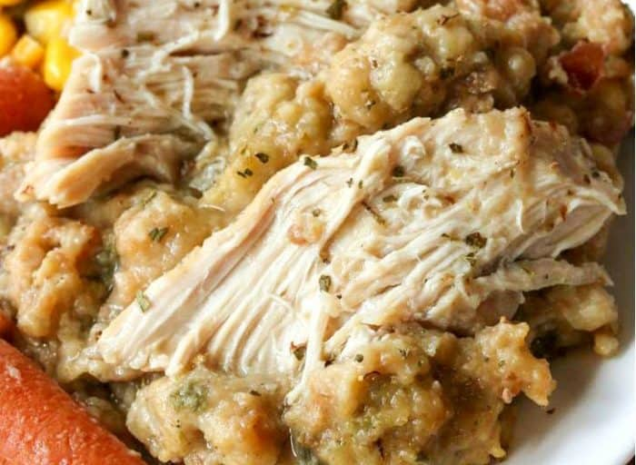 Juicy chicken on top of a pile of stuffing with carrots and corn.
