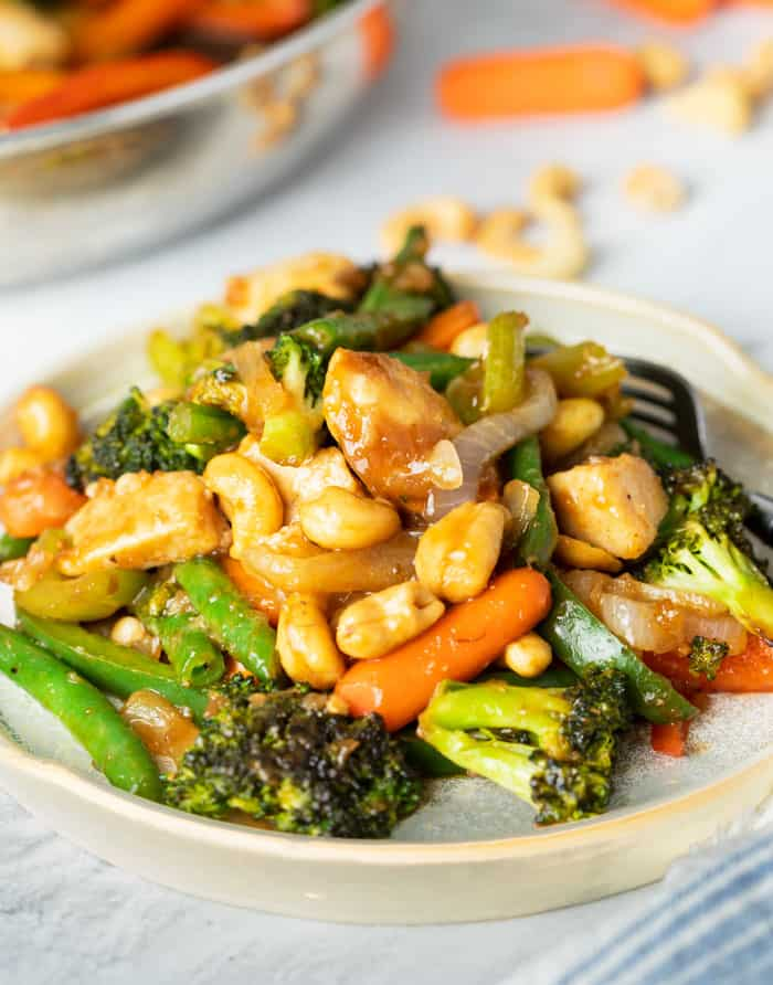 A plate with chicken stir fry topped with cashews.
