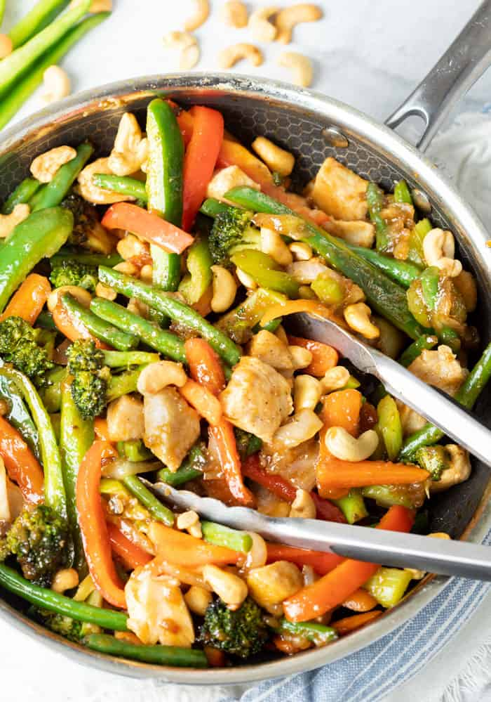 A skillet filled with vegetables and chicken for chicken stir fry.