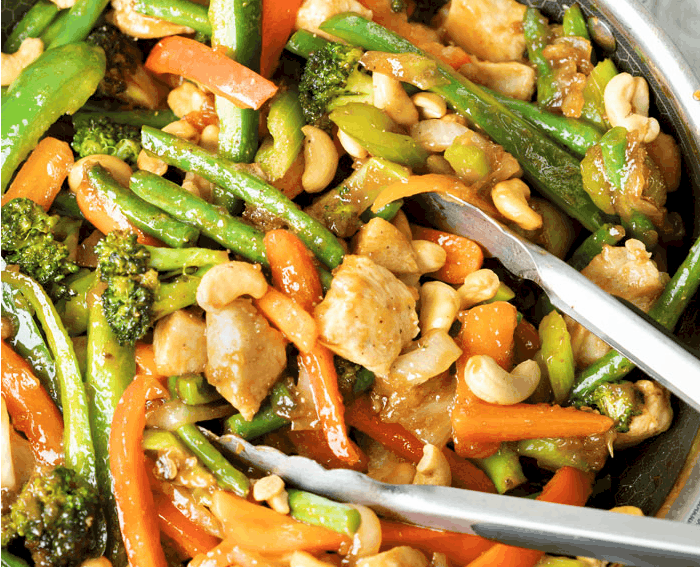 A skillet filled with chicken stir fry with tongs in it. Topped with cashews.