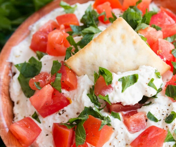 A close up view of a bowl of whipped garlic feta dip topped with diced tomatoes, parsley, and a chip in the middle.