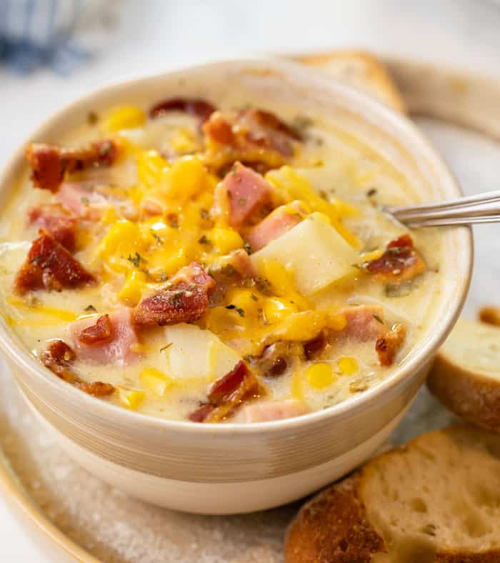 A bowl of ham and potato soup with melted cheese on top.